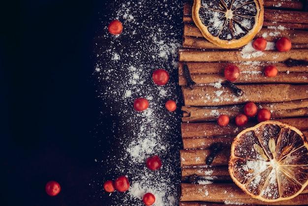 Padaria de natal e ano novo conceito. fundo de férias com fatias de limão cítrico secas, conjunto de paus de canela e baunilha em pó. cozimento acolhedor do feriado de inverno, quadro quente do vinho no fundo escuro.