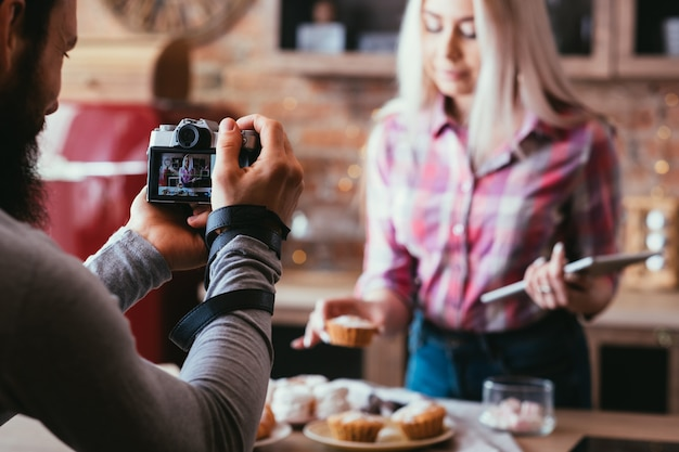 Padaria doce caseira. fotografia de alimentos. homem tirando fotos de uma mulher loira com bolos e doces frescos.