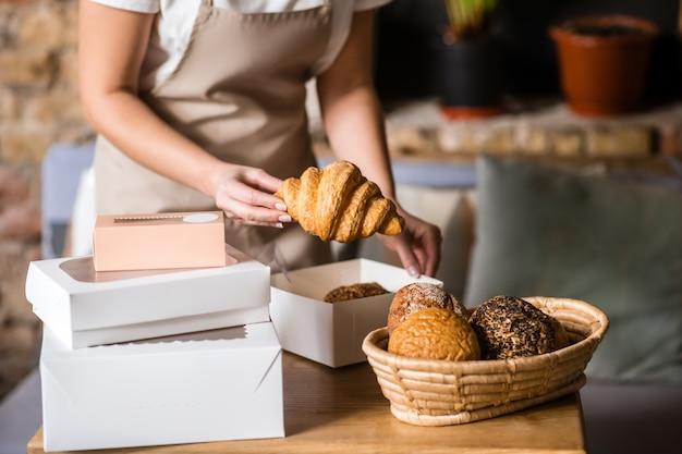 Padaria fresca. graciosas mãos femininas segurando um apetitoso croissant fresco sobre a caixa de embalagem na mesa da padaria