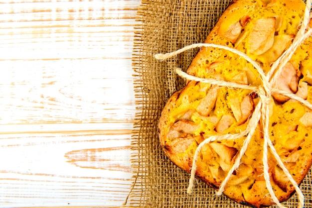 Padaria fresca. vista superior da torta cozida com maçãs de pano de saco em um branco de madeira. estilo rústico.