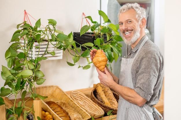 Padaria. homem adulto feliz com sorriso de dentes brancos em pé perto da vitrine da padaria mostrando um croissant fresco e apetitoso