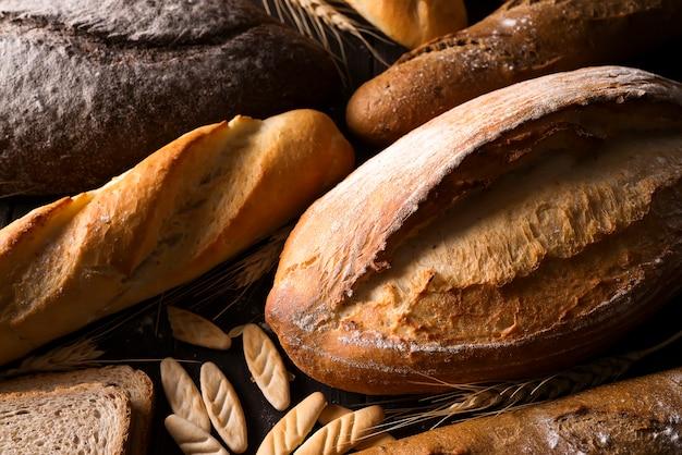 Padaria - pães de pão rústicos rústicos do ouro e bolos no fundo preto do quadro.