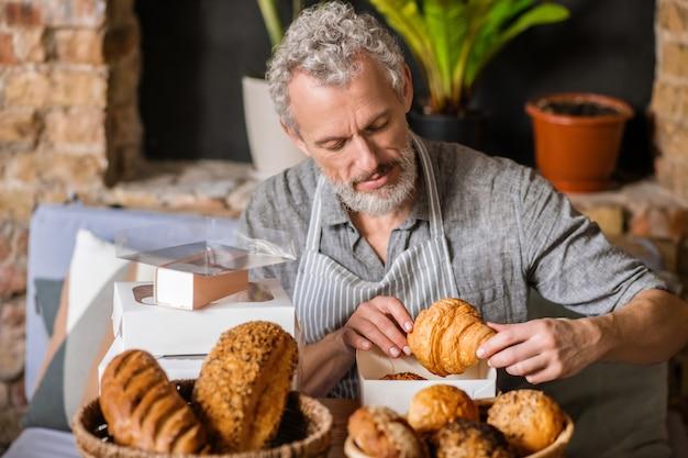 Padaria, pequena empresa. homem barbudo de cabelos grisalhos e atento e focado, embalando ordenadamente o croissant em uma caixa sentado à mesa na confeitaria