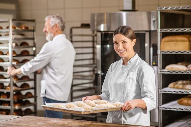 Padaria, trabalho. mulher sorridente com bandeja de croissants crus e homem andando atrás com uma prateleira de pão na padaria