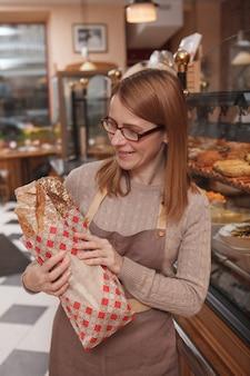 Padeira orgulhosa olhando um pão recém-assado em sua padaria