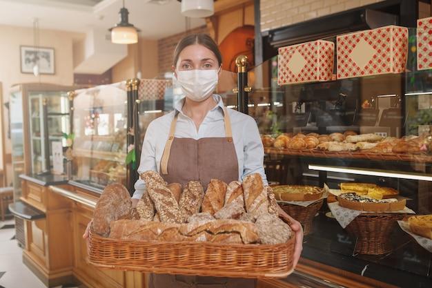 Padeira usando máscara médica e segurando uma cesta cheia de pães recém-assados