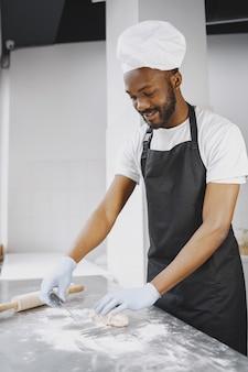 Padeiro afro-americano preparando massa crua para pastelaria na fabricação de panificação.