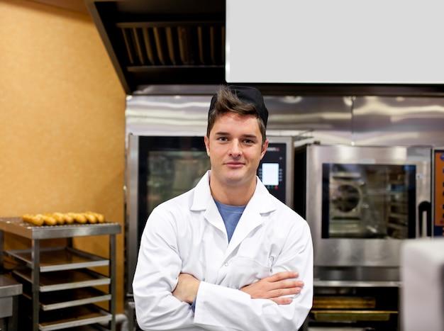 Padeiro alegre que está em sua cozinha com baguettes e fogão no fundo