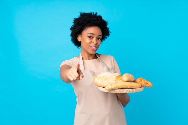 Padeiro americano africano, segurando uma mesa com vários pães