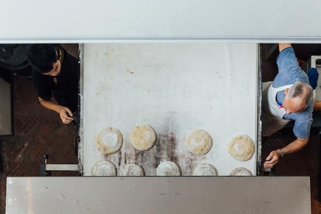 Padeiro artesão ensina seu aprendiz a fatiar a massa de pão de fermento antes de assar