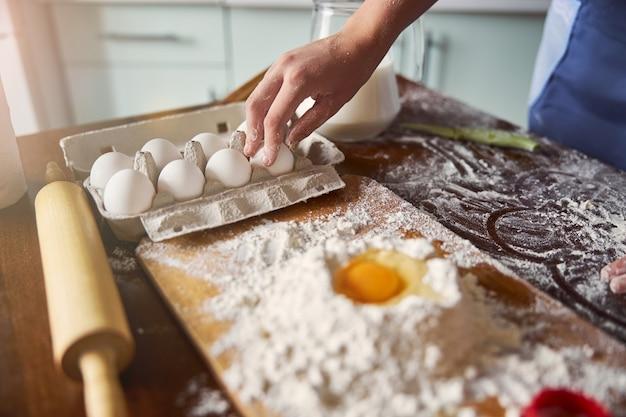 Padeiro atento pegando um ovo para adicionar à mistura de massa