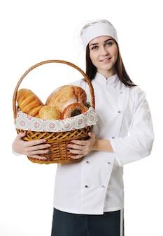 Padeiro bonito da moça no uniforme branco que guarda uma cesta com produtos da padaria em um fundo branco.