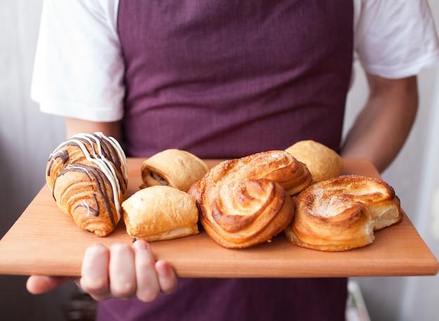 Padeiro bonito de uniforme segurando uma bandeja cheia de croissants recém-assados