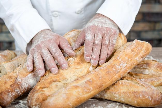 Padeiro com pão francês baguetes tradicionais