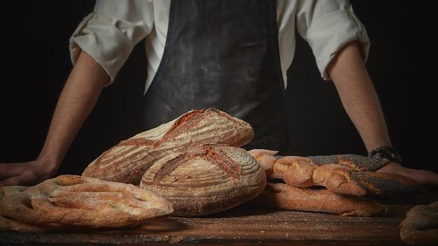 Padeiro com pão fresco na mesa de madeira marrom