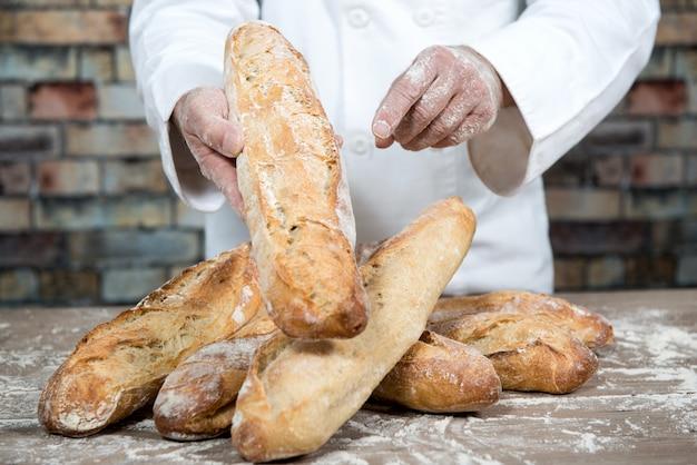 Padeiro com pão tradicional francês baguetes