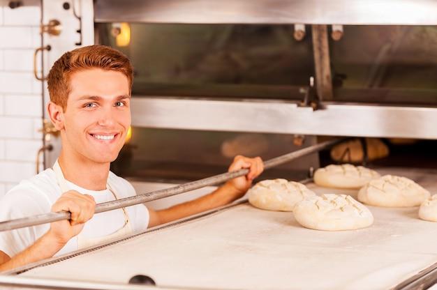 Padeiro confiante. jovem padeiro confiante colocando massa no forno e sorrindo
