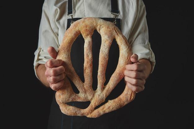 Padeiro de avental segurando pão fougas em um fundo preto isolado