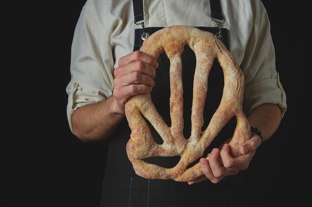 Padeiro de avental segurando um pão fougas orgânico caseiro
