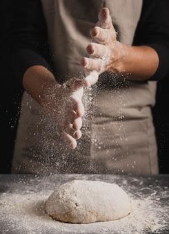 Padeiro de close-up, espalhando a farinha sobre a massa
