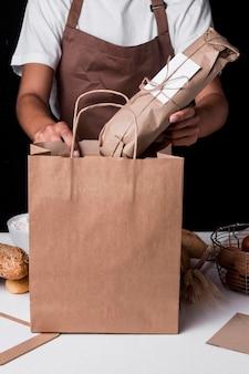 Padeiro de frente colocando o pão embrulhado em um saco de papel