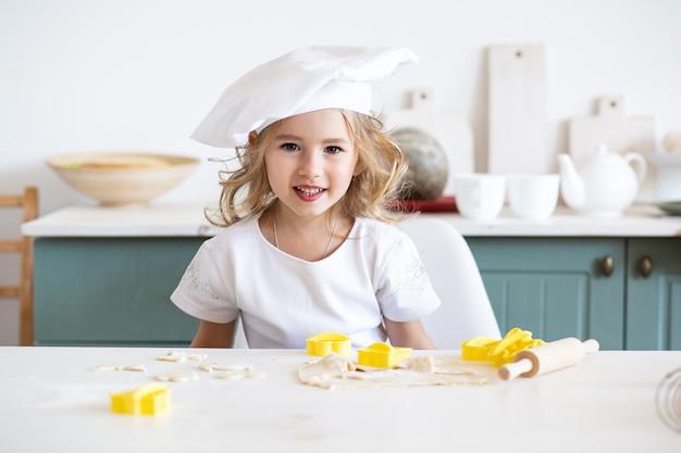 Padeiro de menina bonitinha na cozinha com ingredientes de panificação