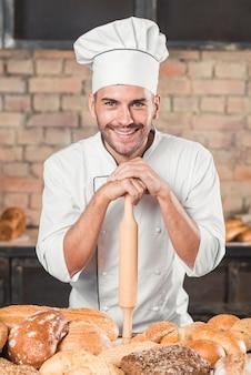 Padeiro em pé atrás da mesa com variedade de pães assados