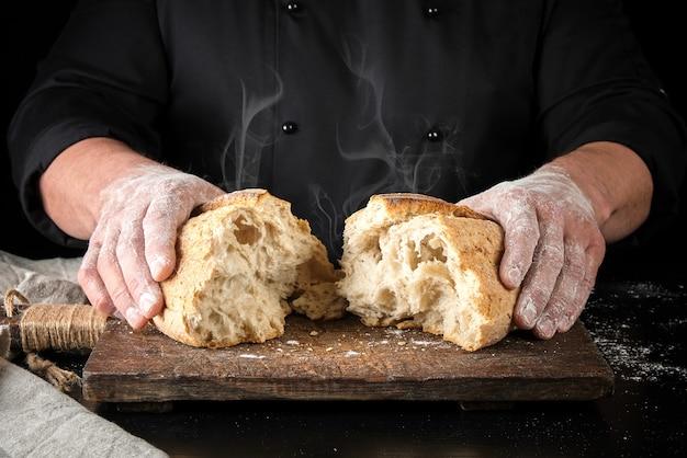 Padeiro em uniforme preto quebrou em meio um pão inteiro assado de pão de farinha de trigo branco
