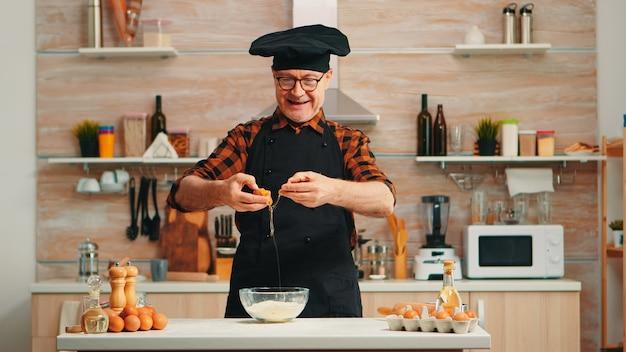 Padeiro experiente craking ovos para assar usando avental, desfrutando de hobby. chef idoso aposentado que mistura bonete à mão, amassando ingredientes de massa em uma tigela de vidro e preparando bolo caseiro