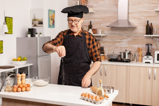 Padeiro experiente na cozinha preparando pizza deliciosa com farinha de trigo bio. chef sênior aposentado com bonete e avental, em uniforme de cozinha, polvilhando ingredientes peneirados com a mão.