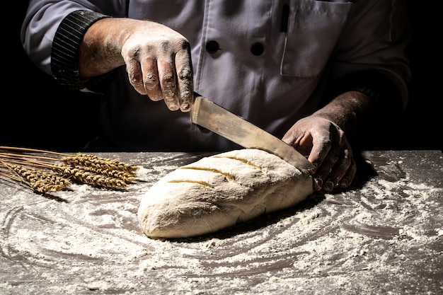 Padeiro fazendo padrões em pão cru usando uma faca para modelar a massa antes de assar