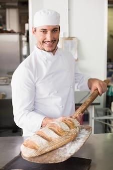 Padeiro feliz tirando pão fresco na cozinha da padaria