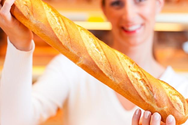 Padeiro feminino em sua padaria com baguete