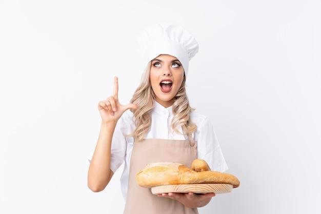 Padeiro feminino segurando uma mesa com vários pães apontando com o dedo indicador uma ótima idéia