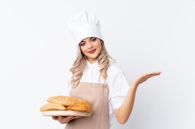 Padeiro feminino segurando uma mesa com vários pães sobre fundo branco isolado, segurando copyspace imaginário na palma da mão