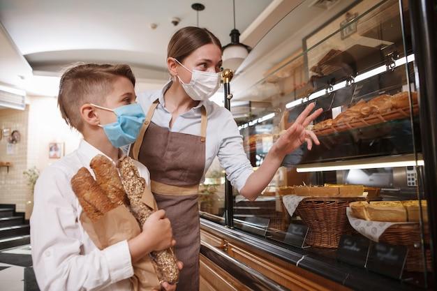 Padeiro feminino usando máscara médica, ajudando seu jovem cliente a escolher sobremesas em exposição de varejo