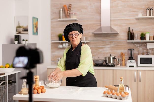 Padeiro idosa apresentando receita de comida em podcast de cozinha de culinária. influenciador chef de blogueiro aposentado que usa tecnologia da internet para se comunicar, fazer blogs nas redes sociais com equipamento digital