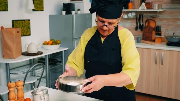 Padeiro idoso adicionando farinha em peneira metálica e polvilhando a massa. chef idoso e feliz com uniforme de cozinha, misturando, polvilhando, adicionando, peneirando, espalhando ingredientes crus para assar pão tradicional