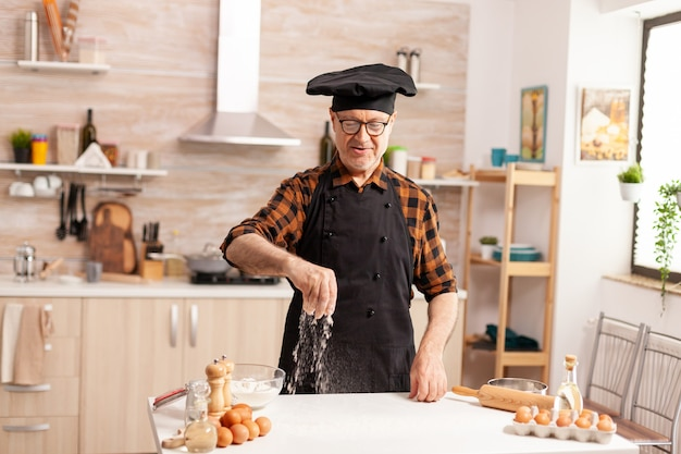 Padeiro idoso preparando comida saborosa usando farinha de trigo bio usando avental e bonete. chef sênior aposentado com bonete e avental, em uniforme de cozinha, polvilhando ingredientes peneirados com a mão.