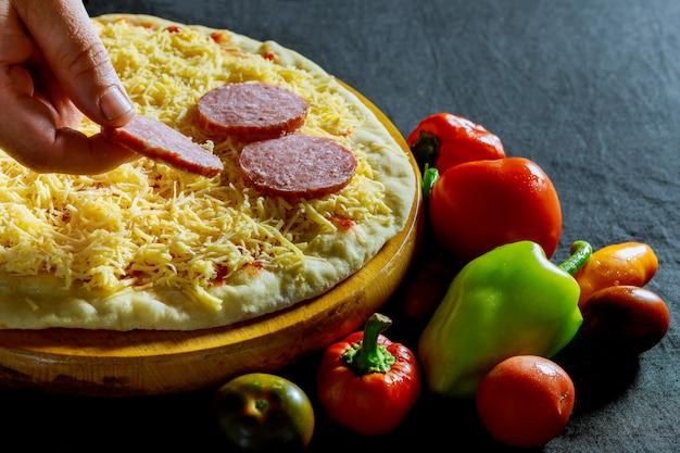 Padeiro, mão, colocar, ingredientes, linguiça, pizza