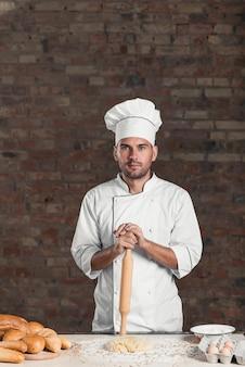 Padeiro masculino em pé atrás da mesa com massa; ingredientes; e pão assado