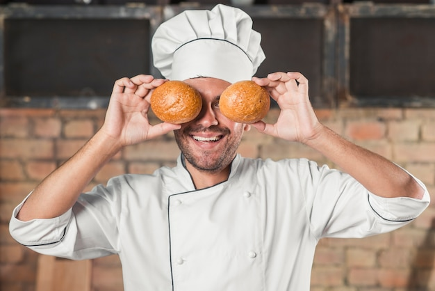 Padeiro masculino novo de sorriso que prende o bolo sobre os olhos