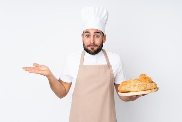 Padeiro masculino segurando uma mesa com vários pães isolados na parede branca, tendo dúvidas com a expressão facial confusa