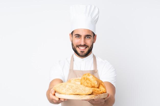 Padeiro masculino segurando uma mesa com vários pães isolados na parede branca