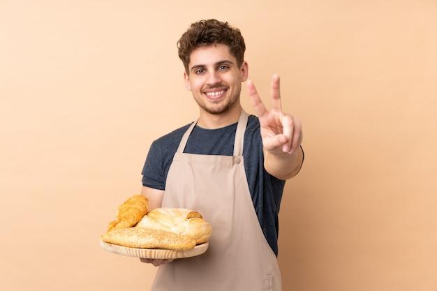 Padeiro masculino segurando uma mesa com vários pães na parede bege sorrindo e mostrando sinal de vitória