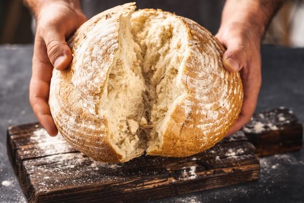 Padeiro partindo pão recém-assado