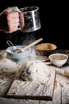 Padeiro peneirar a farinha por uma peneira na mesa de madeira