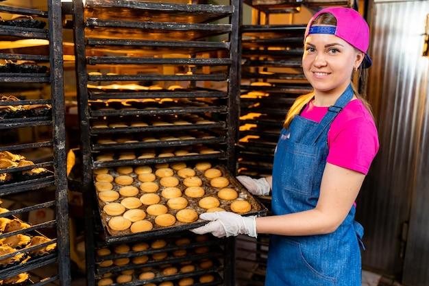 Padeiro profissional. mulher jovem e bonita de uniforme. bandeja de pão fresco no contexto de uma padaria ou fábrica de pão. a produção de panificação.