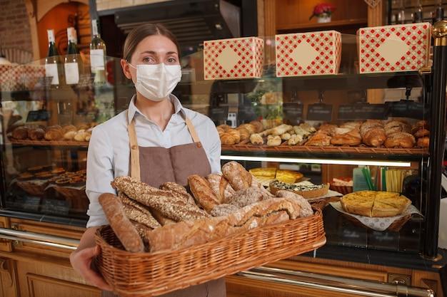 Padeiro profissional que vende pão delicioso em sua padaria durante a quarentena de coronavírus, usando máscara facial