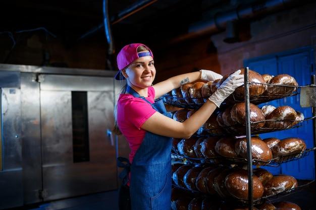 Padeiro profissional - uma jovem bonita com um avental jeans tem pão fresco nas mãos. produtos de confeitaria. produção de pão